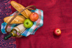 Picnic basket on the red blanket top view. Apples, white wine an Royalty Free Stock Photos