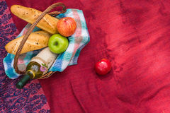 Picnic basket on the red blanket top view. Apples, white wine an Stock Photos