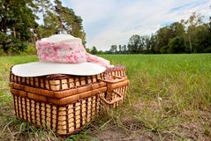 Picnic basket with straw hat Stock Photography