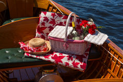 Picnic basket and strawhat in a boat Royalty Free Stock Photos