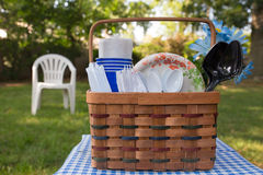 Picnic Basket. Summer day picnic basket with plastic cutlery and paper plates in outdoor setting Royalty Free Stock Image