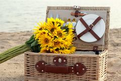 Picnic. Basket and sunflowers o the beach Royalty Free Stock Images