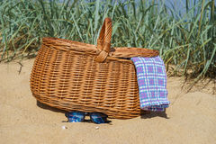 Picnic basket and sunglasses on the beach. Picnic basket with blue white checkered napkin and sunglasses on sandy beach. Weekend break concept Royalty Free Stock Photo