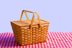 Picnic Basket on Table. A brown wicker antique picnic basket on a gingham tablecloth in front of a blue sky Royalty Free Stock Photo