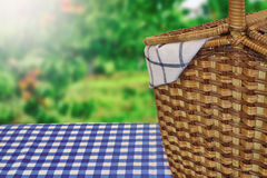 Picnic Basket On The Table With Blue Checkered Tablecloth. Closeup Of Picnic Basket On The Table With Blue Checkered Tablecloth And Summer Garden In The Royalty Free Stock Photos