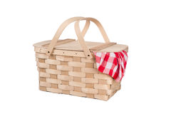 Picnic basket and table cloth. A new wicker and wood picnic basket with a red checkered tablecloth peeking out the side. Isolated on white Stock Photography