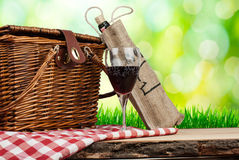 Picnic basket on the table with glass of wine Royalty Free Stock Images