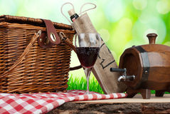 Picnic basket on the table with glass of wine and tun.  stock images
