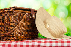 Picnic basket on the table and hat Royalty Free Stock Photo
