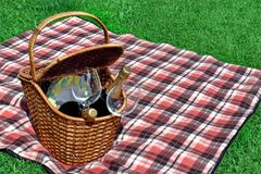 Picnic Basket With Two Wine Bottles On The Red Blanket. Outdoor Picnic Scene, Basket With Two Wine Bottles Wineglasses, Plate On The Red Blanket, Summer Lawn On Stock Photos