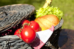 Picnic Basket With Vegetables And Bread. Open Picnic Basket With Tomatoes, Bread, Salad And Champagne On Old Wooden Table Stock Photos