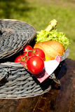 Picnic Basket With Vegetables And Bread. Open Picnic Basket With Tomatoes, Bread, Salad And Champagne On Old Wooden Table Royalty Free Stock Photography