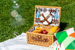 Picnic Basket On White Blanket With Pillows And Soap Bubbles. Picnic Basket Food On White Blanket With Pillows And Soap Bubbles Stock Image