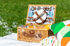 Picnic Basket On White Blanket With Pillows And Soap Bubbles. Picnic Basket Food On White Blanket With Pillows And Soap Bubbles Stock Images