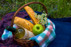 Picnic basket with white wine, two baguettes, green apple and a Stock Images