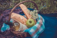 Picnic basket with white wine, two baguettes, green apple and a Royalty Free Stock Photo