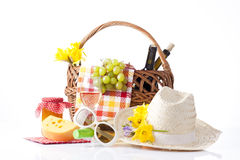 Picnic basket with wine and fruits and summer hat Royalty Free Stock Image