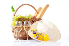 Picnic basket with wine and fruits and summer hat Stock Photography
