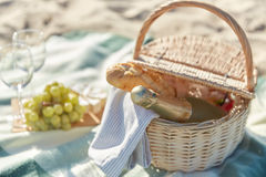 Picnic basket with wine glasses and food on beach. Food, holidays and celebration concept  - close up of picnic basket champagne bottle and french roll bread on Royalty Free Stock Photos
