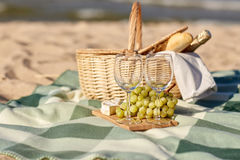Picnic basket with wine glasses and food on beach Stock Photos