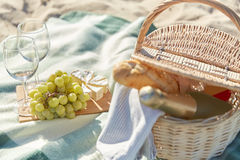 Picnic basket with wine glasses and food on beach. Food, holidays and celebration concept - close up of picnic basket with grapes, wine glasses, cheese and Royalty Free Stock Photo