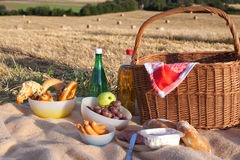 Picnic basket wit food and drinks on field. Picnic basket wit food and drinks on golden straw field Royalty Free Stock Photo