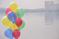 Balloons. On the pier reservoir and city smog background Stock Photography