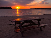 Picnic Beach. A picnic table set on a beach at sunset stock images