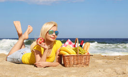 Picnic on the Beach. Blonde Young Woman with Basket of Food. On the Shore Royalty Free Stock Photo