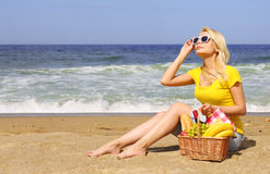 Picnic on the Beach. Blonde Young Woman with Basket of Food Royalty Free Stock Photo