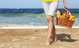 Picnic on the Beach. Female Legs and Basket with Food Royalty Free Stock Images