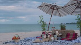 Picnic on the beach. Food and beverages are placed on the table, there is a place to sit and an umbrella to protect from the sun.