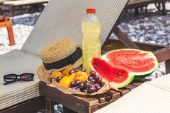 Picnic at the beach. fresh fruits on the table near sun loungers. Summer vacation stock photo
