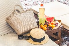 Picnic at the beach. fresh fruits on the table near sun loungers. Summer vacation royalty free stock photos