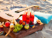 Picnic on the beach at sunset in the boho style Stock Photos