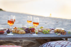 Picnic on the beach at sunset in boho style, food and drink conc Stock Photography