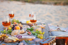 Picnic on the beach at sunset in boho style, food and drink conc. Picnic on the beach at sunset in the style of boho, food and drink conception stock images