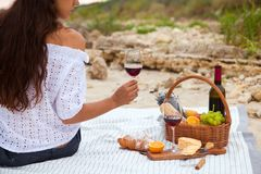 Picnic on the beach at sunset in the white plaid, food and drink. Young woman in Summer Picnic on the beach at sunset in the white plaid, food and drink Royalty Free Stock Images