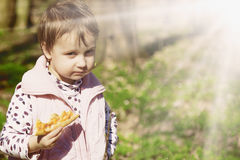 Picnic. Beautiful little girl enjoying a delicious pizza in nature (food, hunger, pleasure) stock images