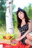 Picnic. Beautiful woman sitting on the blanket Royalty Free Stock Photos