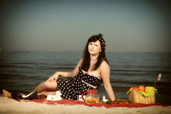 Picnic. Beautiful woman sitting on the blanket Stock Image