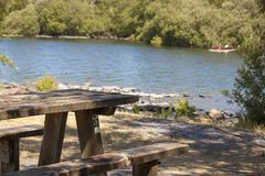 Picnic bench on the shores of Lake Padan, North Wales UK. A wooden table sits on the lake shoreline, with a kayak in the background on a beautiful lake stock image