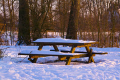 Picnic bench in snow. Picnic bench and table in snow during afternoon sunshine in a park Stock Photos