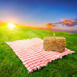 Picnic blanket & basket. Picnic blanket and basket in a sunlit grassy meadow Royalty Free Stock Images