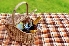 Picnic blanket and basket in the grass. Champagne  wine and glasses in the basket Royalty Free Stock Photography