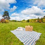 Picnic blanket & basket in sunny field. Picnic blanket, cushion, basket & pillow in a rolling field Stock Image