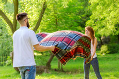 Picnic blanket. Couple in love placing a picnic blanket on a meadow. Leisure time and relaxation in nature Stock Image