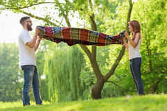 Picnic blanket. Couple in love placing a picnic blanket on a meadow. Leisure time and relaxation in nature Stock Images