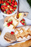 Picnic Blanket with Fresh Bread, Strawberry. Cheese and  honey Stock Photography