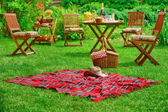 Picnic Blanket With Hat And Basket. Party Or Picnic Concept. Closeup Of Red Picnic Blanket With Cowboy Straw Hat And Basket Or Hamper. Blurred Outdoor Wooden Stock Photography